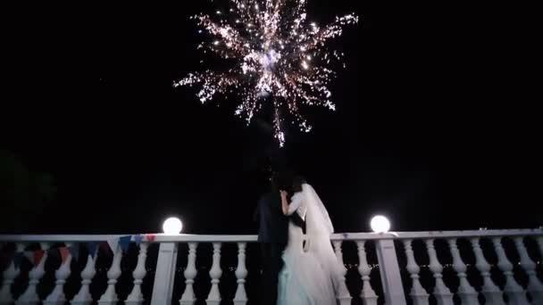 Zadní pohled šťastné líbání novomanželé těší zábavní pyrotechniky v noci