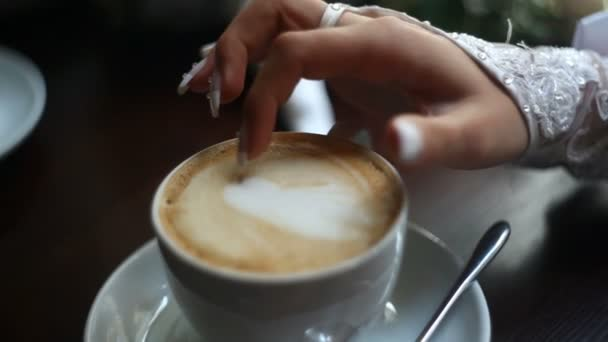The close-up view of the bride finger painting the heart on the cappuccino.