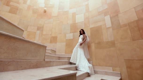 Full-length fottage atraktivní bruneta s dlouhými kudrnatými vlasy a stylové šaty, Pózování na žluté moderní schodiště