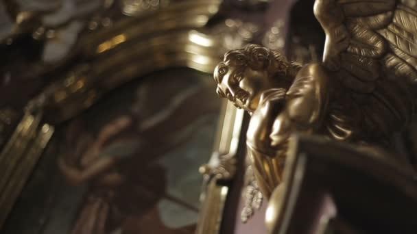 Zlatá socha anděla zdobí barokní kostel.