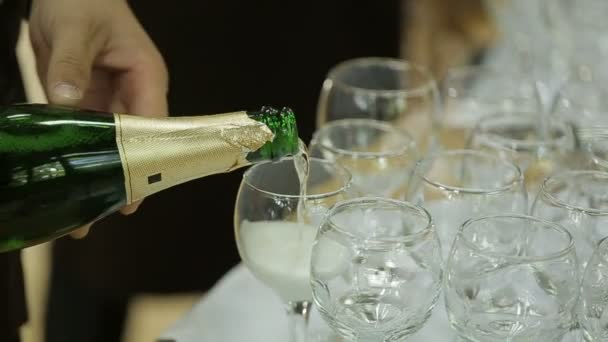 Kellner gießt den Champagner in Gläser auf dem Buffettisch. Hochzeitsbar. Kein Gesicht. Nahaufnahme.