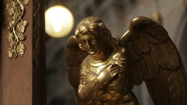Close-up shot zlatá socha anděla zdobí kostel.
