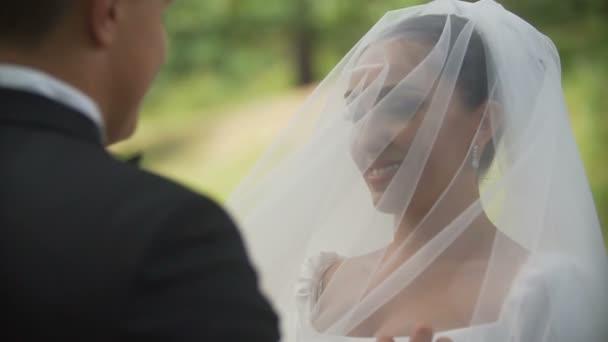 e21c0fcb20 El novio es levantar el velo de la sonriente novia morena hermosa en el  parque. Ver sobre su hombro. Close-up– metraje de stock