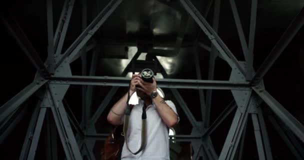 Porträt des gut aussehenden Fotografen, der eine hochmoderne Kamera bereit hält, um Fotos zu machen.