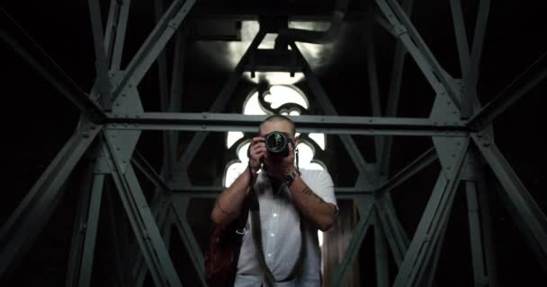 Ein attraktiver junger Fotograf fotografiert in Richtung Kamera. Nahaufnahme. Profi-Fotograf.