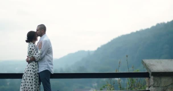 Milující pár stojí venku. muž líbá ženu na čelo. žena si položí hlavu na rameno. lidé v lásce a krásné přírodě