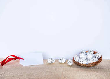 Easter background with eggs in bird nest and empty gift tag sign