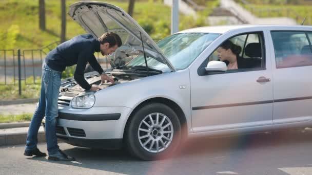 Woman help to man repair broken car