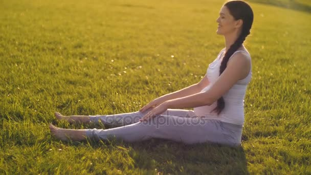 Pregnant woman stretching at the grass