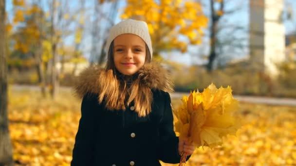 Kislány kezében sárga levelek