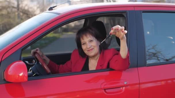Elderly woman showing keys sitting in a car