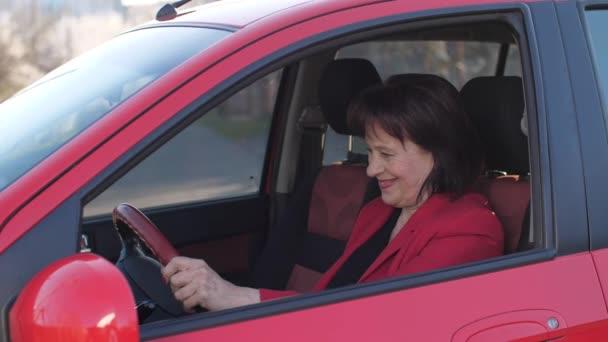 Happy elderly woman in a new car
