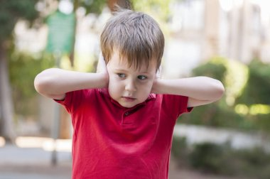 Little Caucasian boy in red polo shirt closing ears with his hands and looking aside.