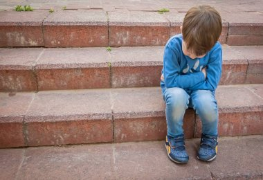 Unhappy little Caucasian child sitting on the stairs in a closed position with his head down.