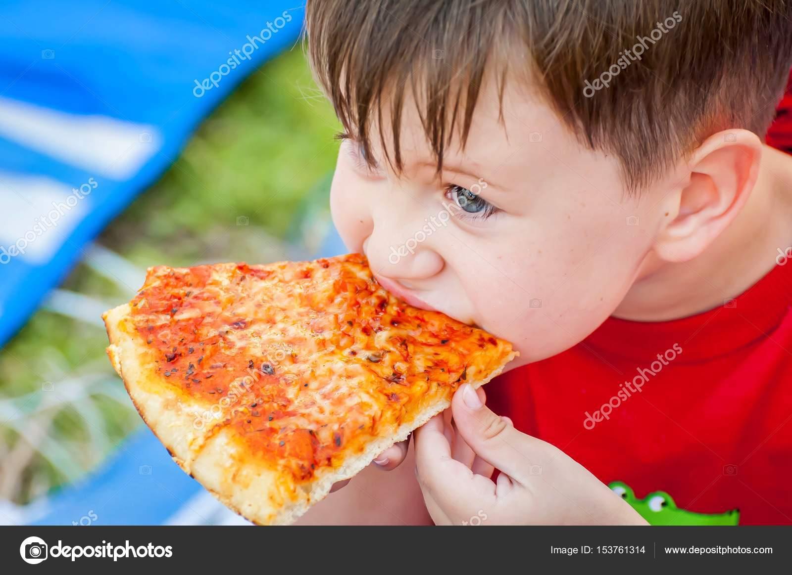 Cute Little Kid Taking A Bite From Delicious Margarita Pizza Slice Photo By Roman Yanushevsky
