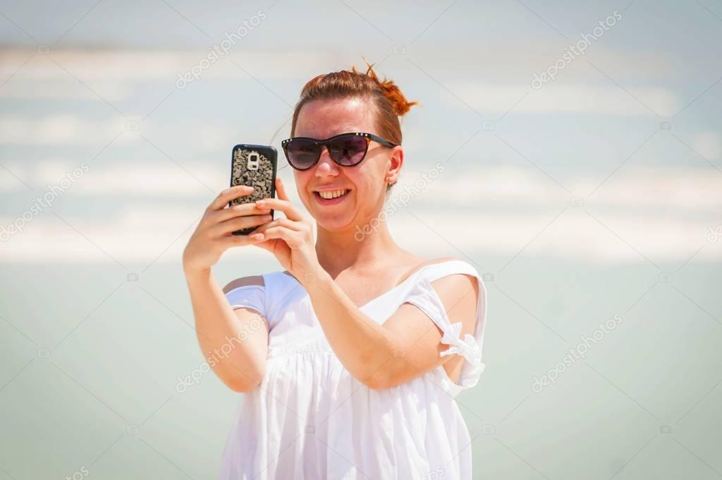 Pretty Russian girl making a selfie at the Dead Sea.