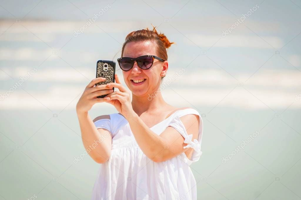 Pretty Russian girl making a selfie at the Dead Sea.