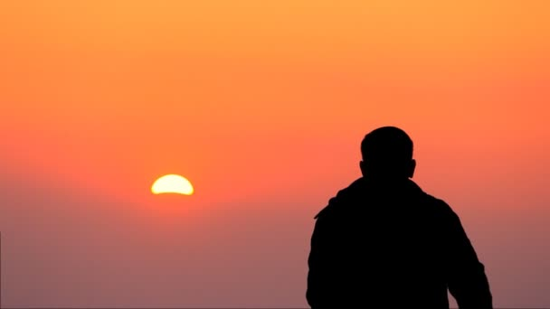 Silhouette of a young guy looking at an orange Sunset