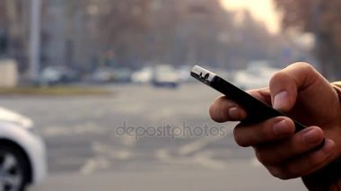 A mans hand uses black smartphone on the background cityscape with cars