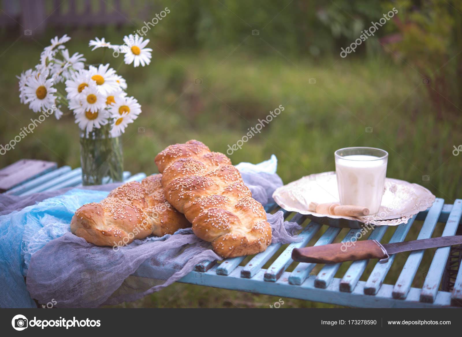 Long pain blé nouvellement cuit à l\u0027extérieur. Challah juif. Pain long une  tresse de sésame sur une table en bois bleue dans la rue \u2014 Image de Gekachka