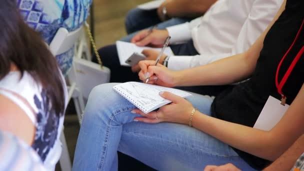 Egy tollat, és notebook tartó szeminárium rendezvényen női.