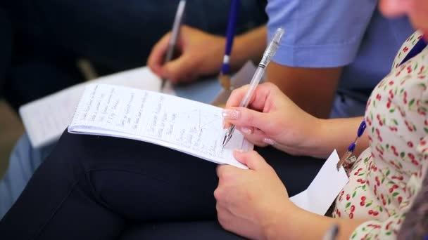 Nő, írja a notebook szeminárium rendezvényen tollal.