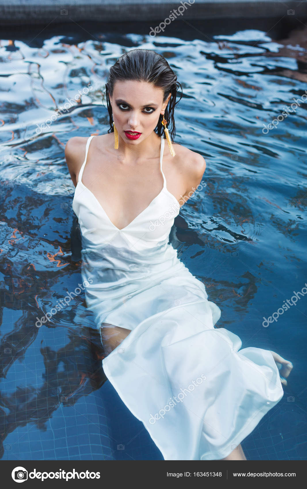 beautiful brunette woman in white wet dress lies in the water. woman