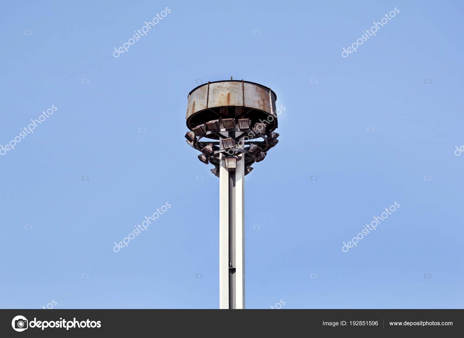 Torre con riflettori alla rotonda sulla strada di città e la strada