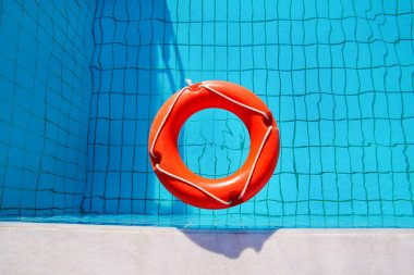 Red lifebuoy pool ring float, ring floating in refreshing blue swimming pool. Red float floating in the pool with blue water. Inflatable red swim ring floating on a pure water with sunny reflections.