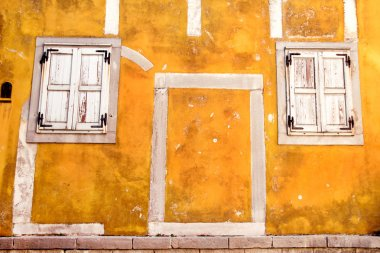Old yellow facade / Classic vintage wood windows at the yellow concrete building / The architectural background, rustic materials and texture, closeup.