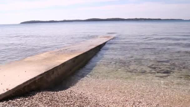 Kamenný molo uprostřed moře s malými vlnami, malé kameny. Starý kamenný molo pro rybaření a Jaderské moře a vlny zřítilo na něm. Krásný výhledem na Středozemní moře. Slunečný letní den