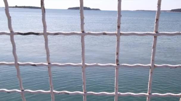 Blick auf Eisenzaun mit blauem Meer im Hintergrund. Sicherheitsnetz mit Blick auf das Meer, Nahaufnahme. ein alter rostweiss gestrichener hoher Stahlzaun mit Himmel und Strand. Mittelmeer, Adria. sonniger Sommertag.