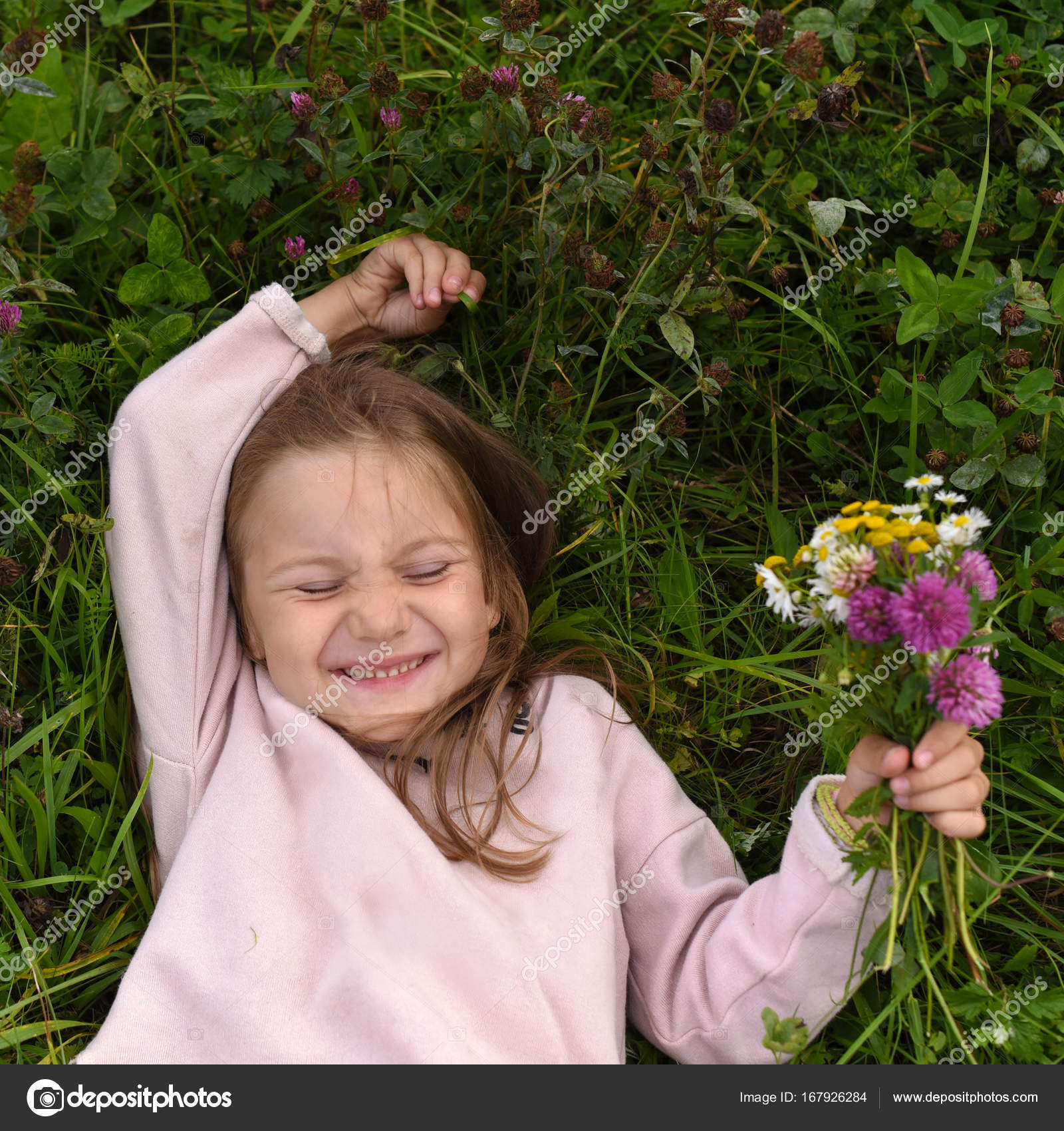 A cute laughing little girl, laying on the grass and ...
