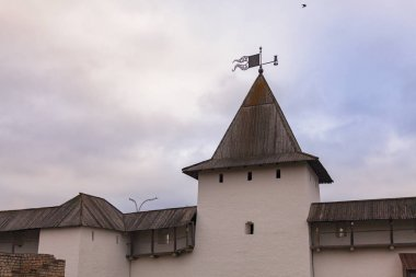 Fragment of the fortress wall with a watchtower at the top of which a weather vane in the shape of a flag is installed