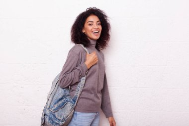 Young cheerful smiling african student girl wearing backpack on a white background