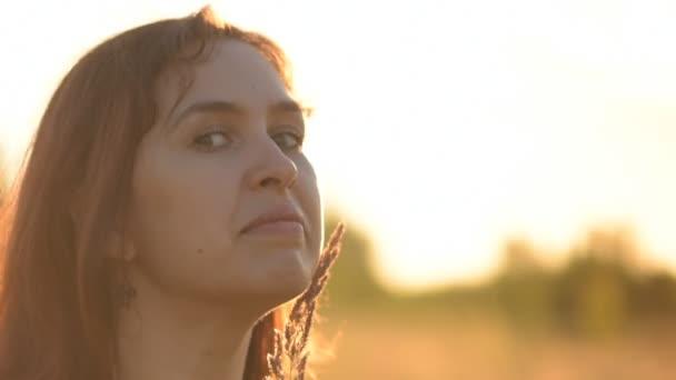 Krásný model dívka na sobě džíny a zelené tričko na hřišti ve slunečním světle. Při pohledu na fotoaparát a smích