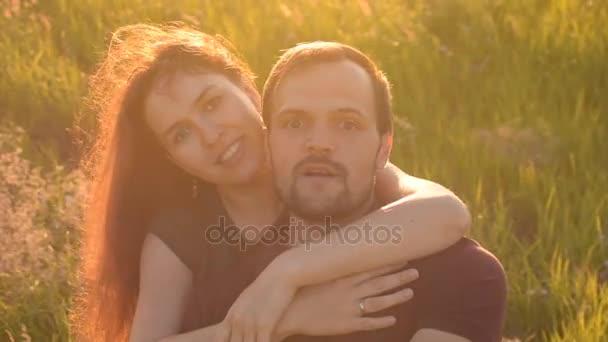 Boldog pár séta a parkban, a naplemente, és figyelembe véve a selfie. Meglepett, hogy néz a kamerába.