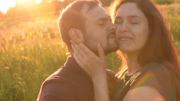 Beautiful romantic couple hugging each other walking in the garden. The young man pressed his face to face her friend and then kisses her.