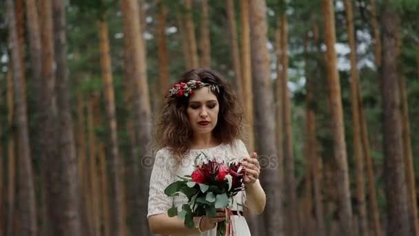 Krásná nevěsta v retro šaty s barevnými kytice čerstvých květin od Vrána na hlavu pod širým nebem v letním lese. Obdivuje její kytice