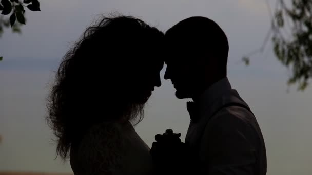 Silhouettes of a man and a young woman. Against the sky in the backlight
