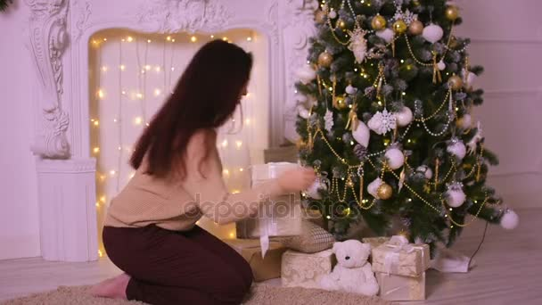 Young woman near fireplace in Christmas puts presents under the Christmas tree for his family.