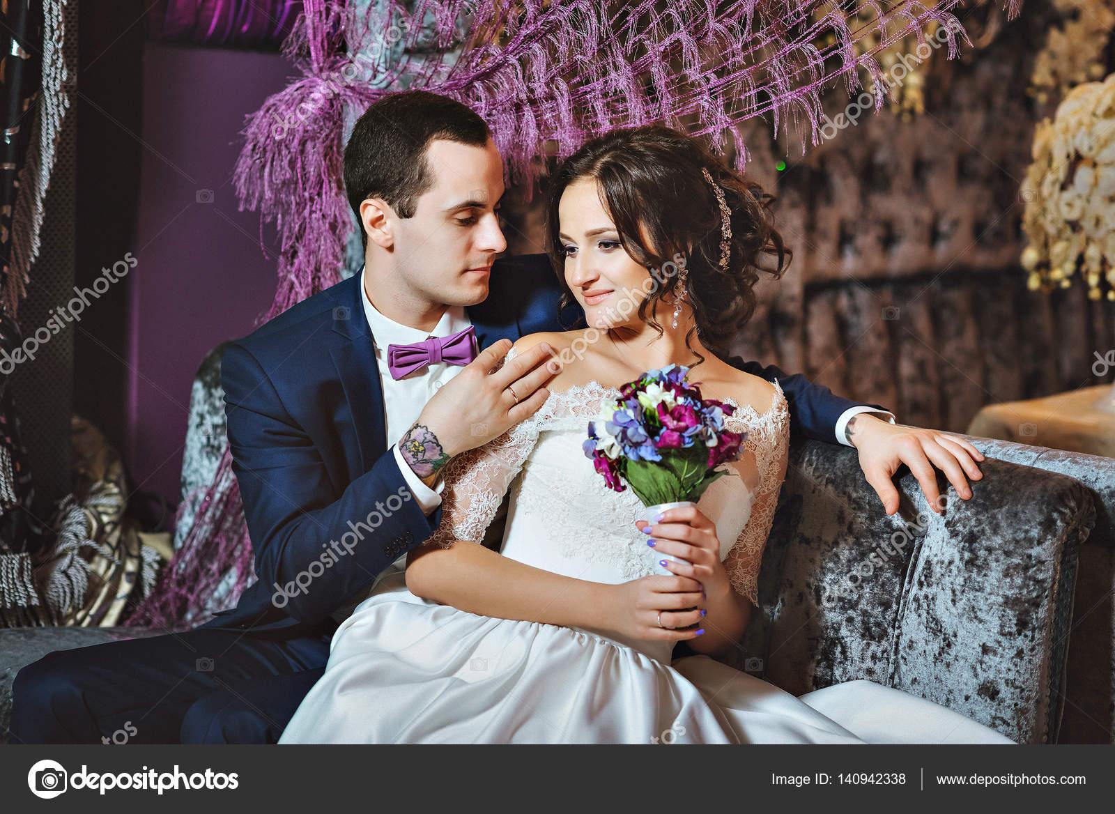 25bee70e4ee3 Bruden och brudgummen i lyxig inredning i lavendel färg. Bröllop känslor.  Vackra brudparet eleganta vid ceremonin– stockbild