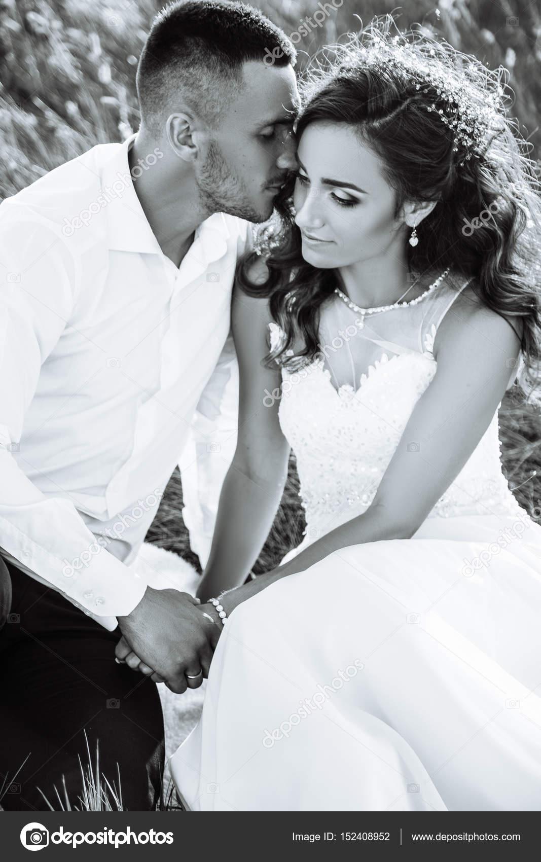 Beau couple dans le champ, amateurs ou jeunes mariés posant sur coucher de  soleil avec un ciel parfait. Émotions réelles.