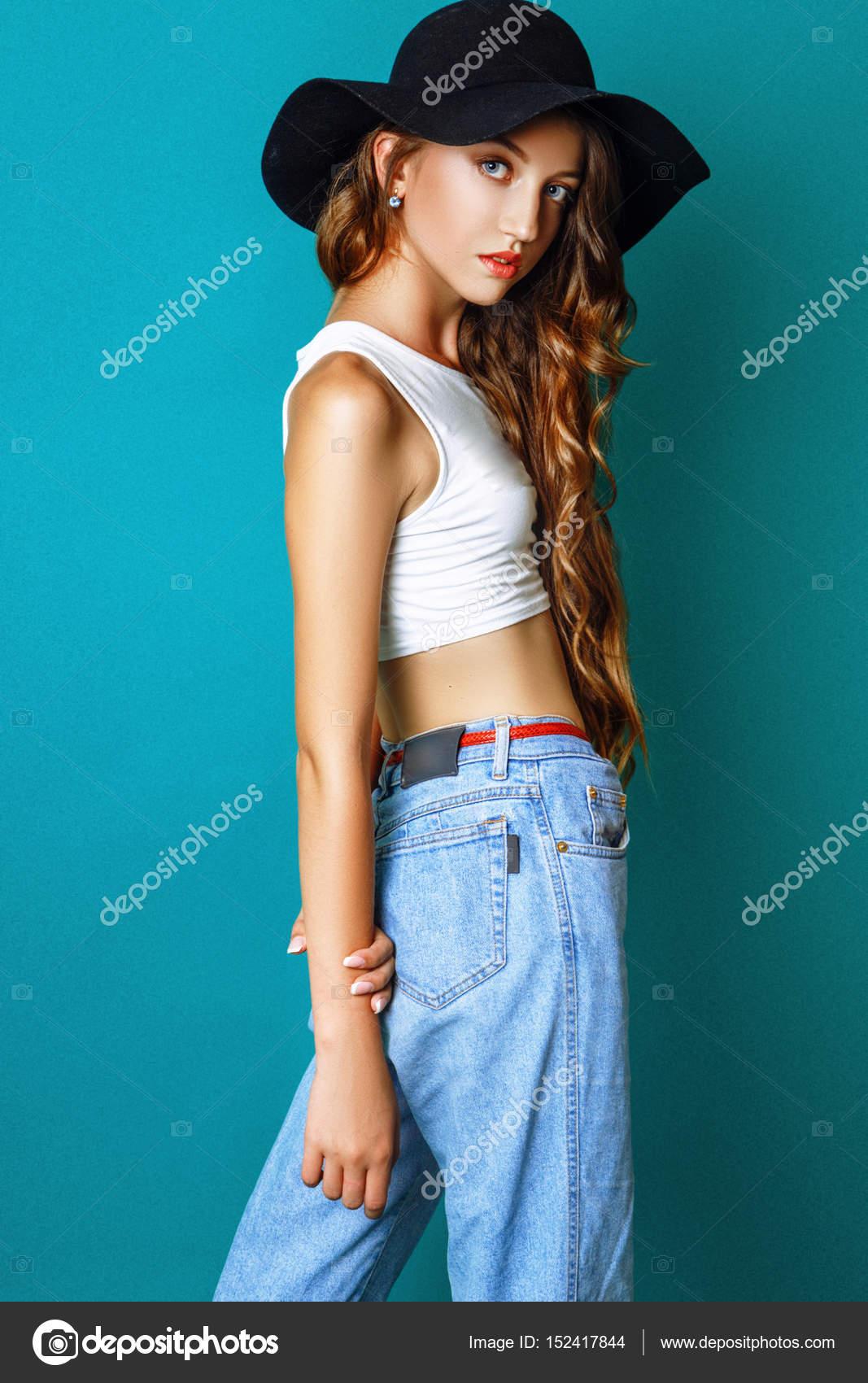 Modefoto jungen Frau auf grünem Hintergrund. Gekleidet in schwarzen Hut,  weißes Top und Jeans. Mädchen posiert. Studio Foto — Foto von YuliiaChupina bc7625d3e6