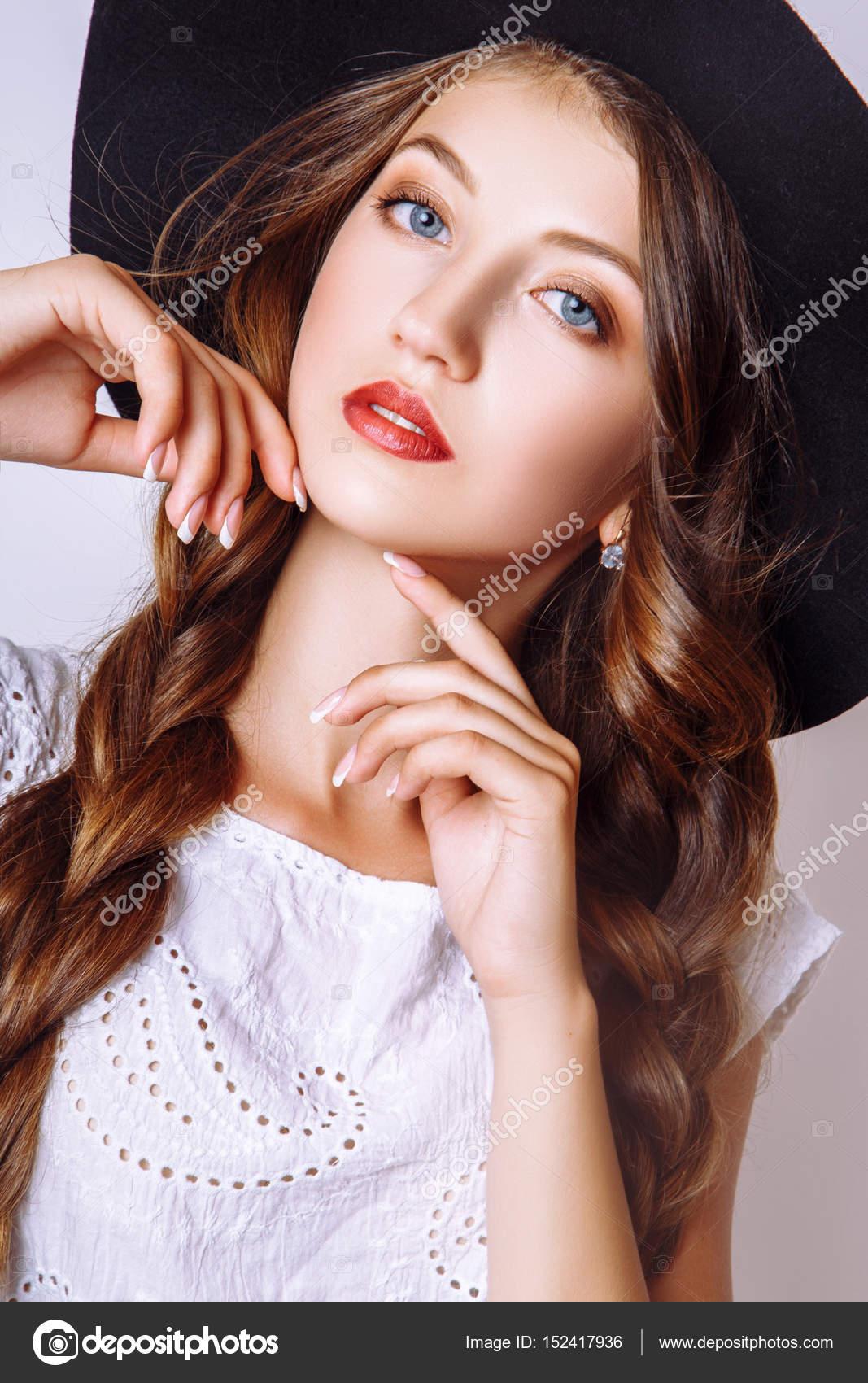 Modefoto jungen Frau auf weißem Hintergrund. Gekleidet in weißen Kleid und  schwarzen Hut. Mädchen posiert. Studio Foto. 7081561b96