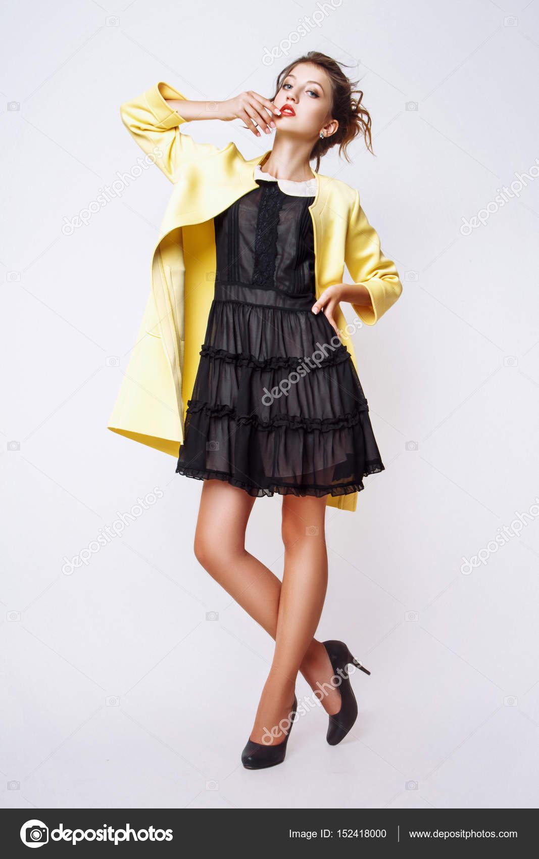 Modefoto jungen Frau auf weißem Hintergrund. Gekleidet in schwarze und  gelbe Mantel. Mädchen posiert. Studio Foto — Foto von YuliiaChupina a0830c028e