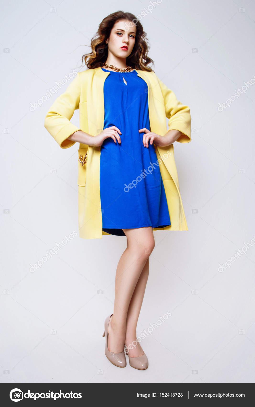 Modefoto jungen Frau auf weißem Hintergrund. Gekleidet in ein blaues Kleid  und einen gelben Mantel. Mädchen posiert. Studio Foto — Foto von  YuliiaChupina 72cecc5be6