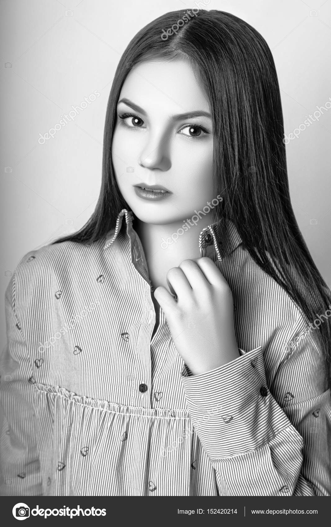 Beautiful teenage girl with long hair on a white background studio photo dressed in a blue blouse and jeans black and white photo by