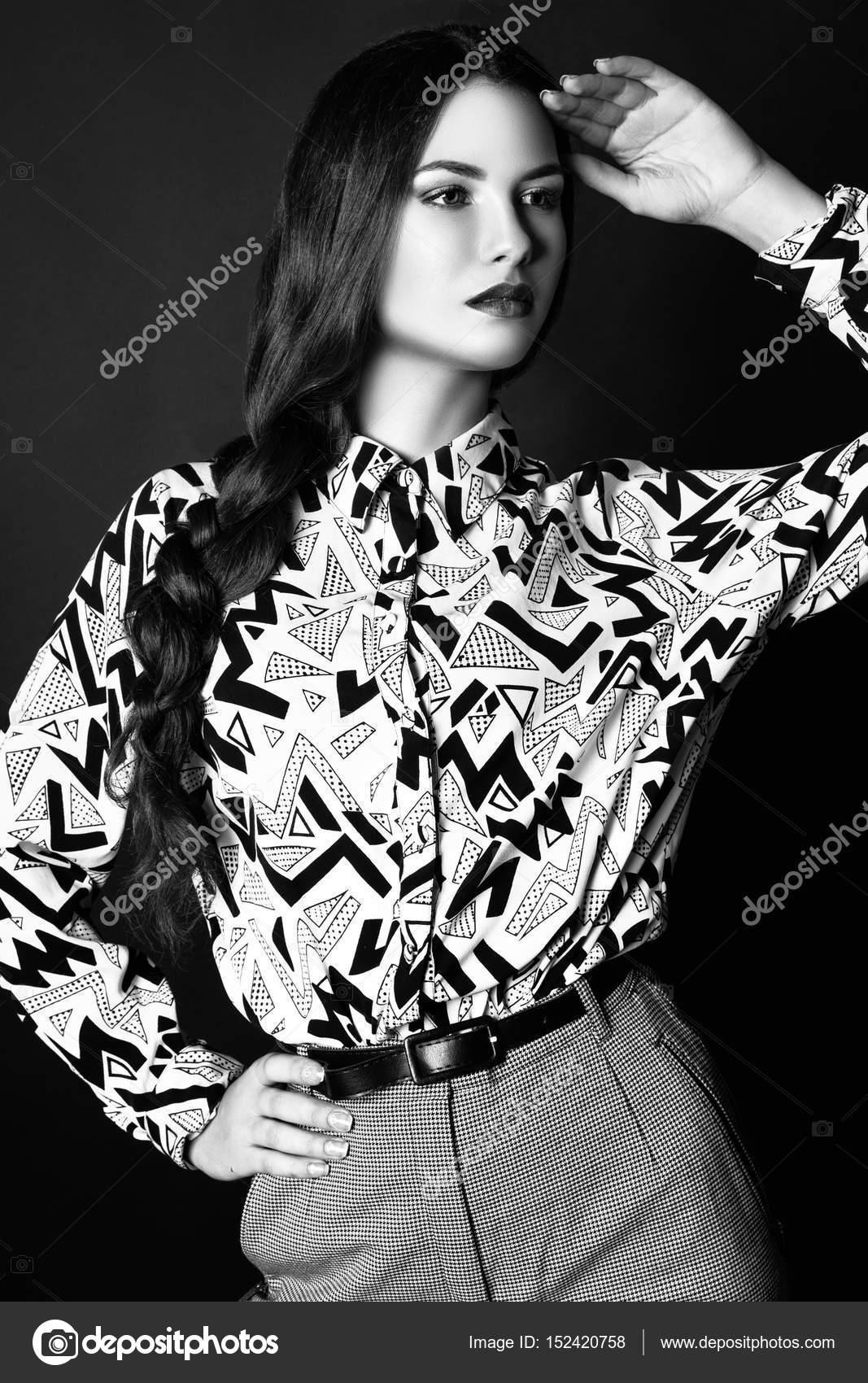 Modefoto jungen Frau auf schwarzem Hintergrund. Gekleidet in ein Hemd und  Hose mit Ornament. Mädchen posiert. Studio Foto. ccd4b3cc1d