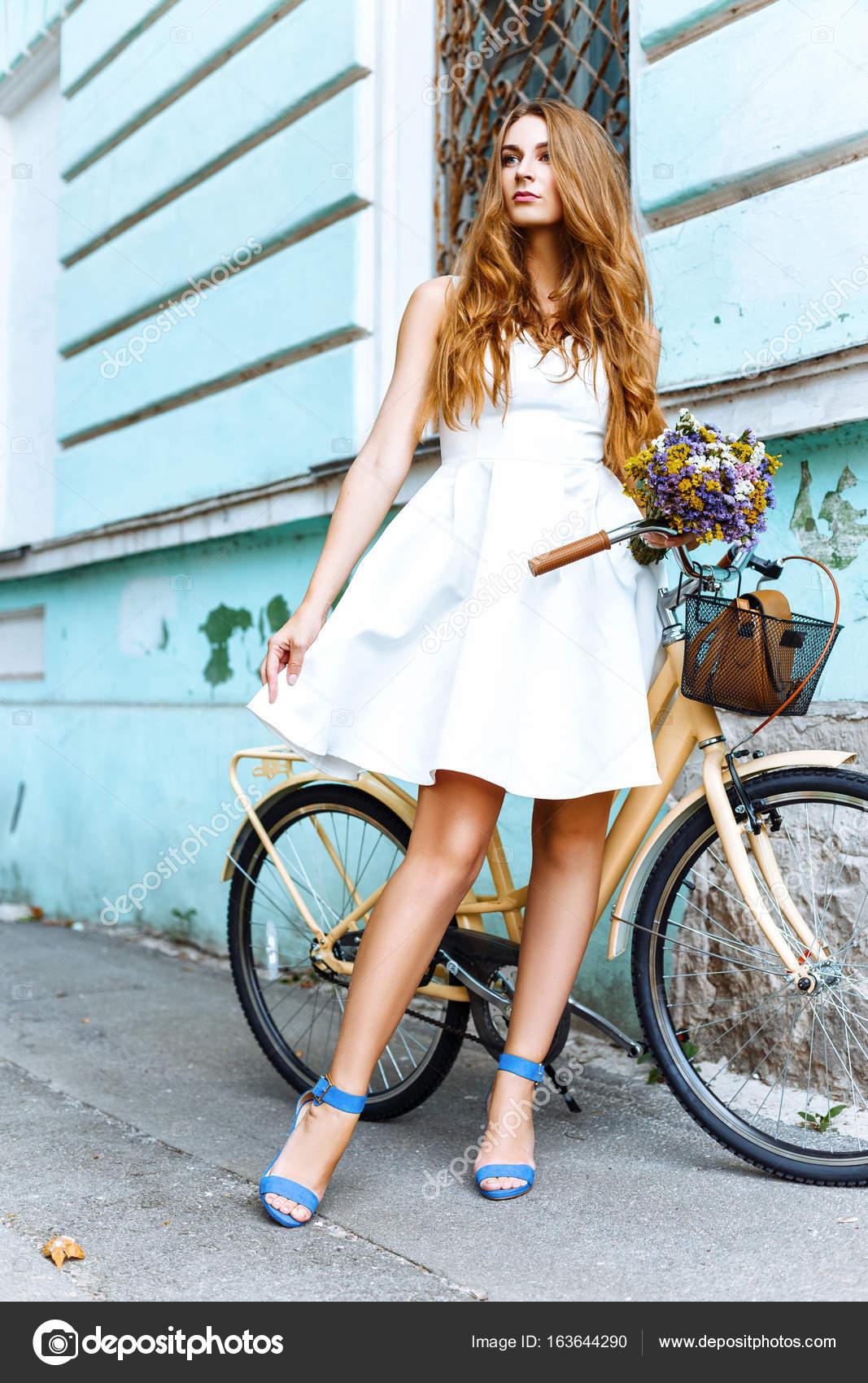 finest selection 609f0 85205 Ragazza in vestito bianco con biciclette e fiori vicino alla ...